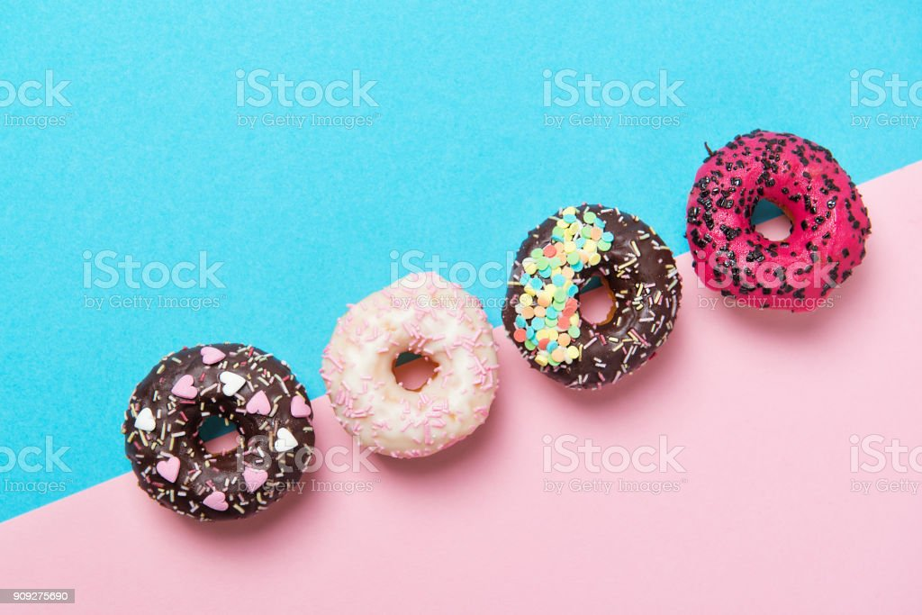 Assorted colored donuts in a row, minimalism on a blue and pink background, top view stock photo