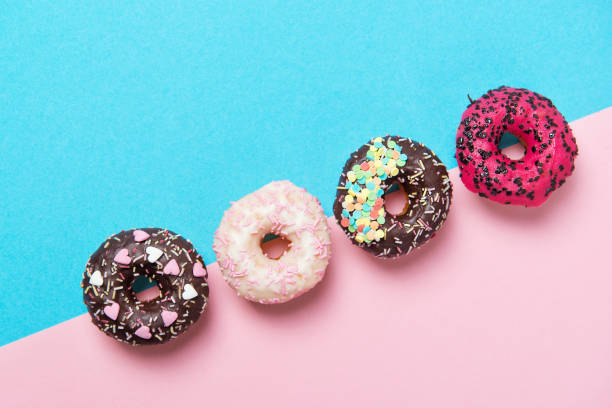 assorted colored donuts in a row, minimalism on a blue and pink background, top view - bombolone foto e immagini stock
