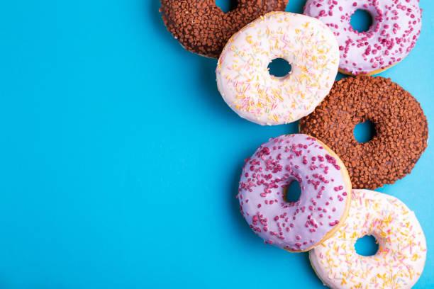 Verschiedene leckere Donuts auf hellen blauen Hintergrund. Fehlerhaft, aber leckere Süßigkeiten – Foto