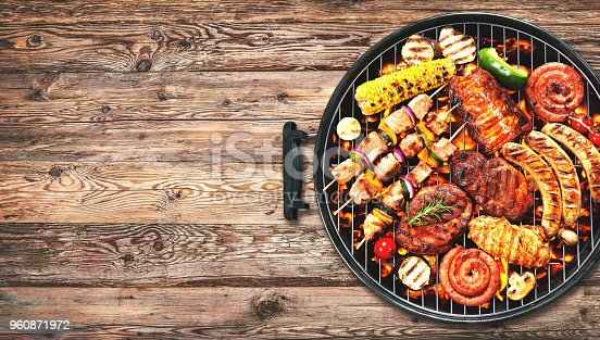 istock Assorted delicious grilled meat and bratwurst with vegetables on grill 960871972