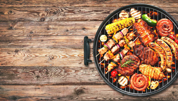 assorted delicious grilled meat and bratwurst with vegetables on grill - barbecue grill stock photos and pictures
