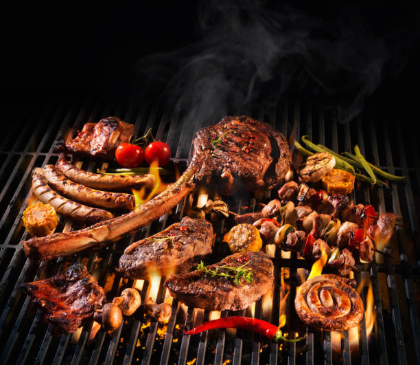 assorted delicious grilled meat on a barbecue - barbecue grill stock photos and pictures