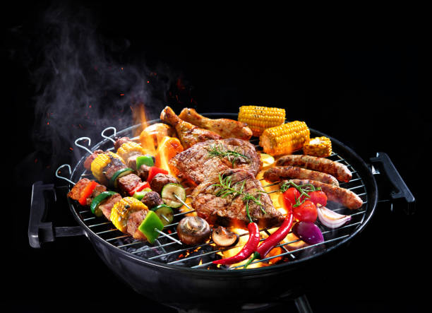 Assorted delicious grilled meat with vegetables on barbecue isolated on black background stock photo