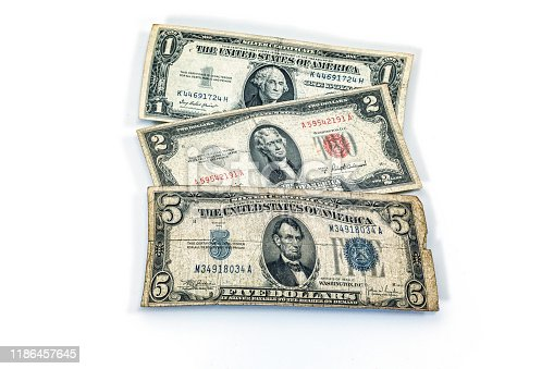 Assorted (deliberately distorted) historic, antique United States paper currency. In front, a 1930s series five dollar denomination Silver Certificate. Next, a 1950s series two dollar denomination United States Note. In back, a 1950s one dollar denomination Silver Certificate.