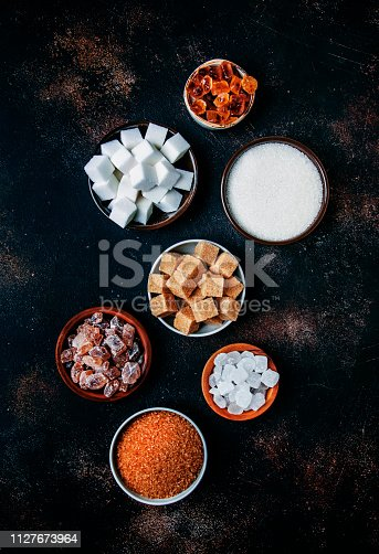 Assorted different types of sugar in bowls on a table on a dark background, vertical image