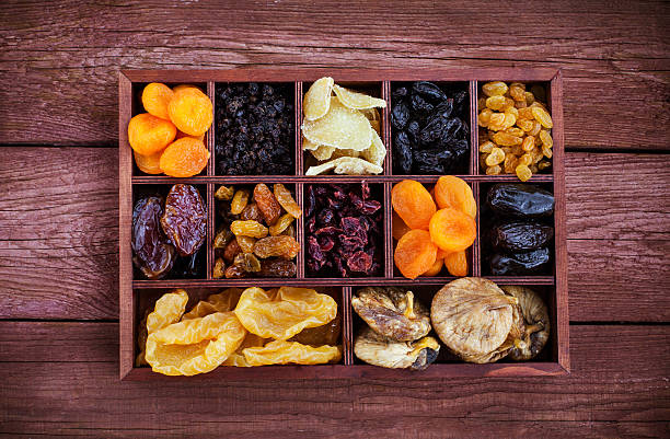 assorted dried fruits in wooden box - dried fruit stock photos and pictures