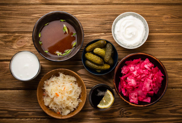Assorted fermented foods Top view of assorted fermented foods and drinks, sources of probiotics great for healthy gut and digestive system: kimchi, pickles, sauerkraut, miso soup, kombucha, yogurt, kefir, wooden background bifidobacterium stock pictures, royalty-free photos & images