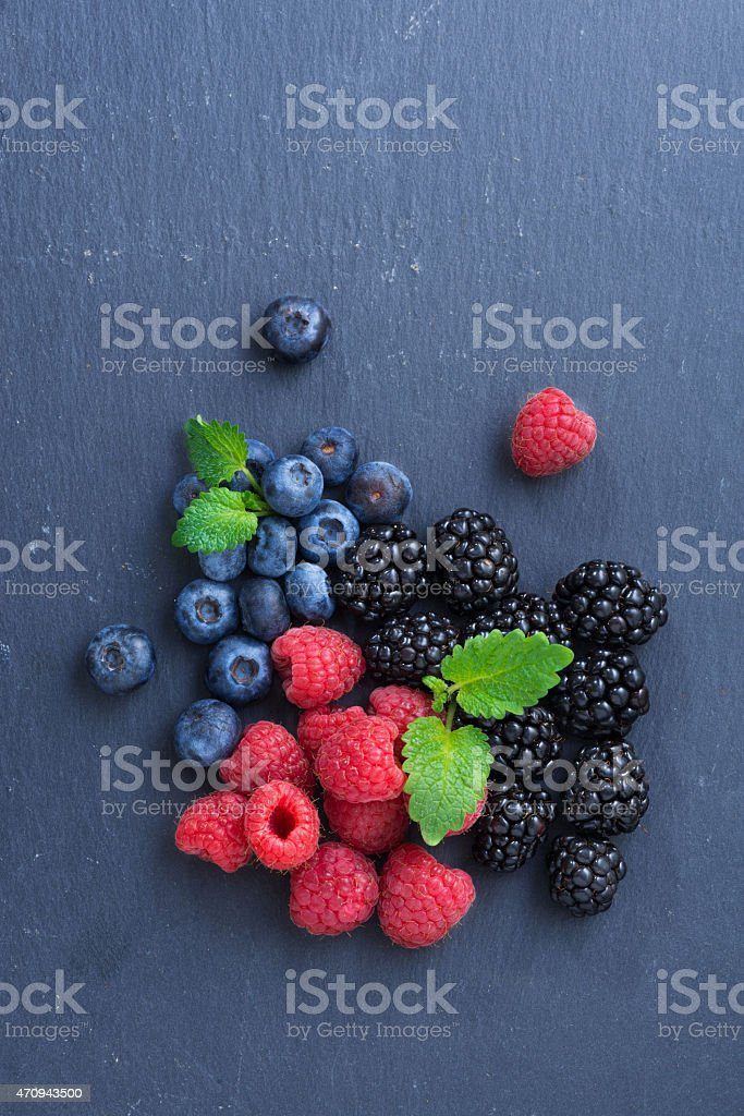 Assorted fresh berries on a black background, top view, vertical stock photo