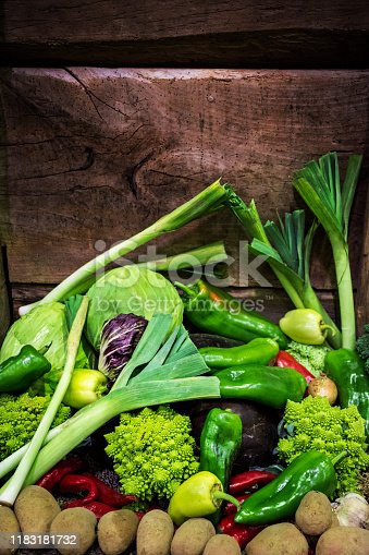 Heap of fresh organic vegetable in the front of an old barn wooden wall. The Composition includes various peppers, leek, romanesco cauliflower, cabbage, onion, garlic, potatoes...