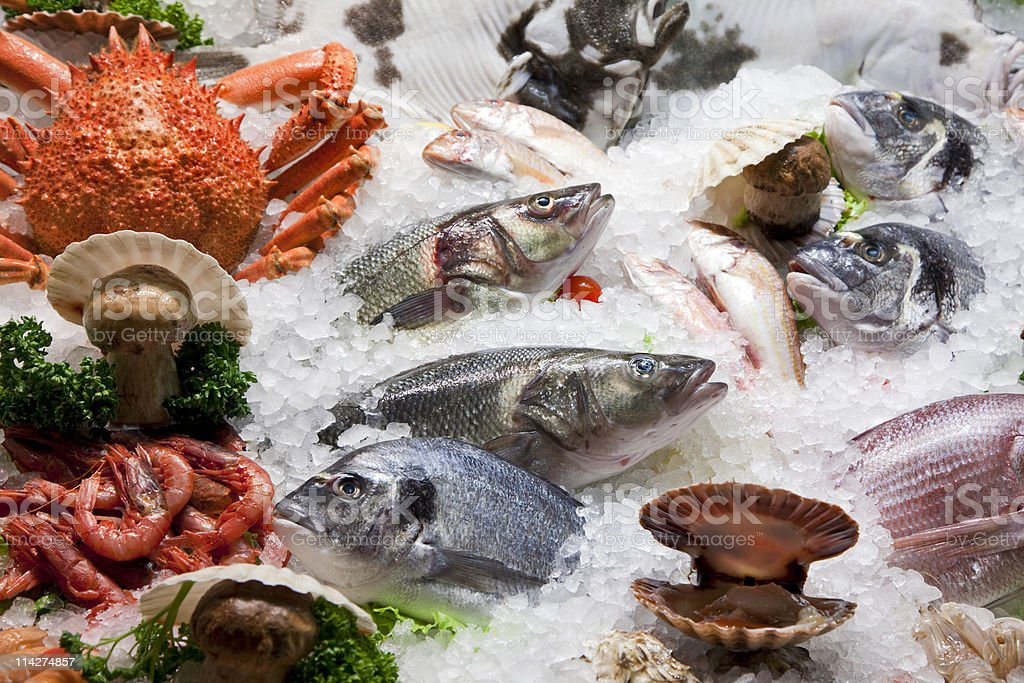 Assorted fresh seafood on ice, including fish, shrimp, crab stock photo