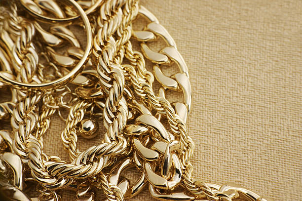 Assorted golden jewelry on brown material stock photo