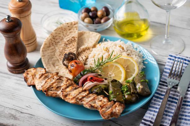 assorted greek food platter with souvlaki, rice, pita and dolmades stock photo