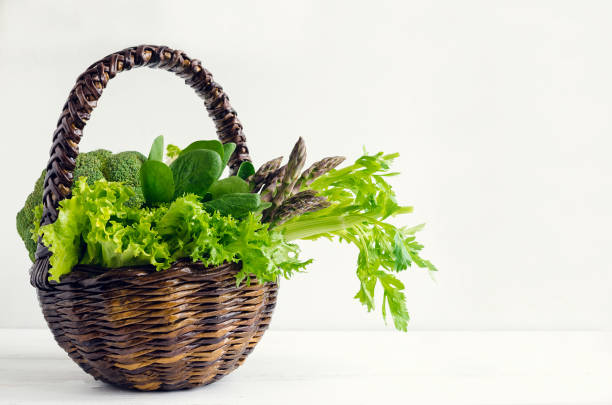 Assorted green vegetables in a basket Assorted green vegetables food background as a healthy eating concept of fresh garden produce organically grown as a symbol of health. Basket with raw greens. Detox, clean eating. Copy space. chlorophyll stock pictures, royalty-free photos & images