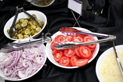 hamburger toppings, tomatoes, onions, pickles and cheese. hamburger toppings in white bowls