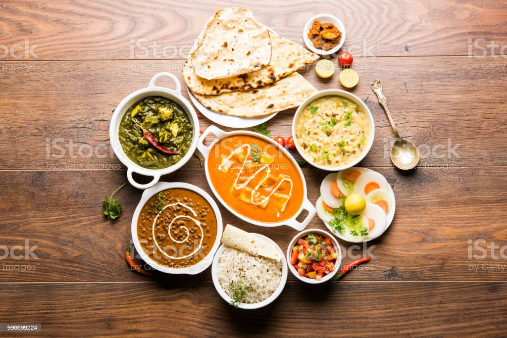 Assorted indian food for lunch or dinner, rice, lentils, paneer, dal makhani, naan, chutney, spices over moody background. selective focus stock photo