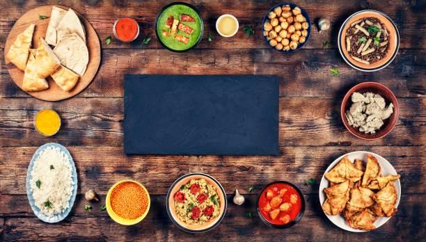 ассорти индийской кухни на деревянном фоне. блюда и закуски индийской кухни. карри, масло курица, рис, чечевица, палак панир, самоса, наан, ча� - food delivery стоковые фото и изображения
