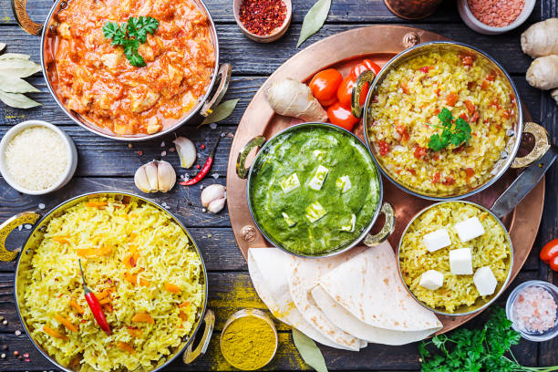Assorted indian food Different bowls with assorted indian food on dark wooden background, top view. Dishes and appetizers of indian cuisine. Chicken, curry rice, lentils, paneer, chapati and spices. curry powder stock pictures, royalty-free photos & images