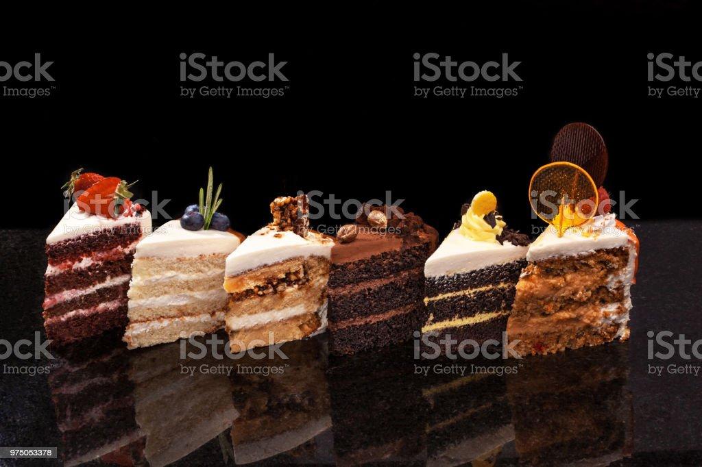 Verschiedene große Stücke von verschiedenen Kuchen: Schokolade, Himbeeren, Erdbeeren, Nüsse, Heidelbeeren. Stück Kuchen auf einem schwarzen Tisch - Lizenzfrei Amerikanische Heidelbeere Stock-Foto