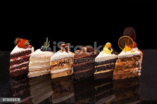 istock Assorted large pieces of different cakes: chocolate, raspberries, strawberries, nuts, blueberries. Pieces of cakes on a black table 975053378