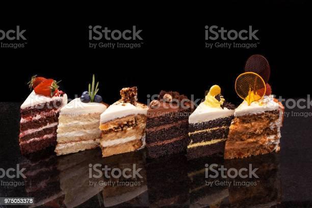 Verschiedene Große Stücke Von Verschiedenen Kuchen Schokolade Himbeeren Erdbeeren Nüsse Heidelbeeren Stück Kuchen Auf Einem Schwarzen Tisch Stockfoto und mehr Bilder von Amerikanische Heidelbeere