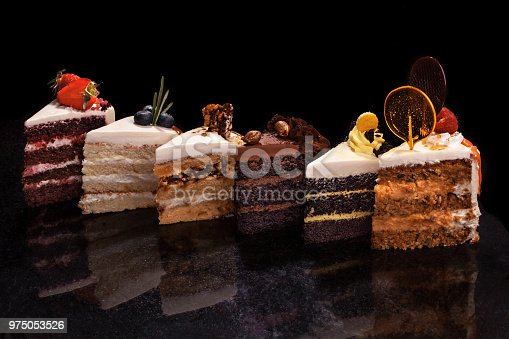 istock Assorted large pieces of different cakes: chocolate, raspberries, strawberries, nuts, blueberries. Pieces of cakes on a black table 975053526