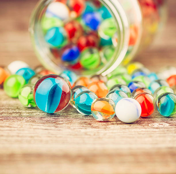 verschiedene marbles auf holztisch verschütten von krug - spielesammlung stock-fotos und bilder