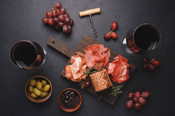 assorted meat appetizers for wine. bresaola, prosciutto, pork neck, pate, jam, olives and grapes. traditional italian meat sausages on black stone background - bresaola foto e immagini stock