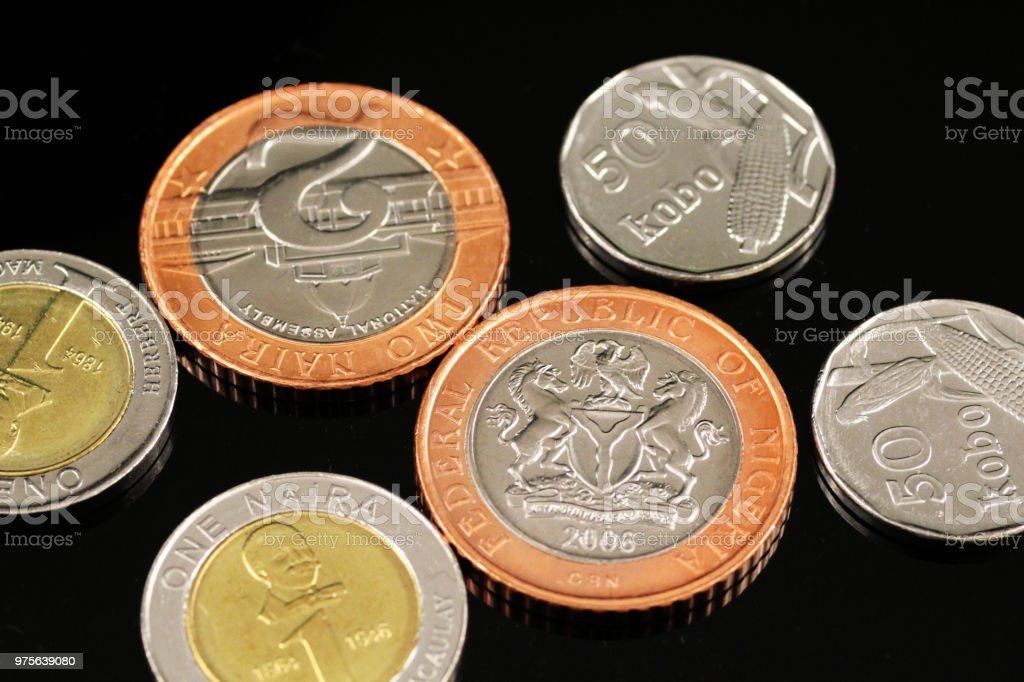 Assorted Nigerian coins on a reflective black background stock photo