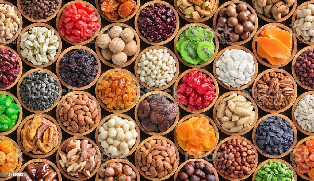 geassorteerde noten en gedroogde vruchten achtergrond. biologisch voedsel in houten kommen, bovenaanzicht. - Royalty-free Abrikoos Stockfoto