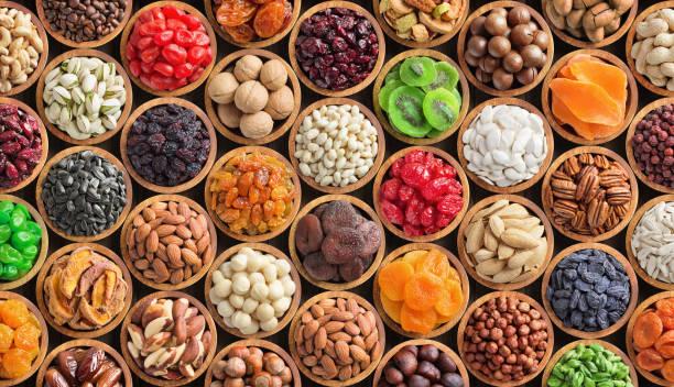 geassorteerde noten en gedroogde vruchten achtergrond. biologisch voedsel in houten kommen, bovenaanzicht. - snack stockfoto's en -beelden