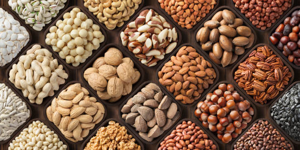 assorted nuts background, large mix seeds. raw food products: pecan, hazelnuts, walnuts, pistachios, almonds, macadamia, cashew, peanut and other - frutos secos imagens e fotografias de stock