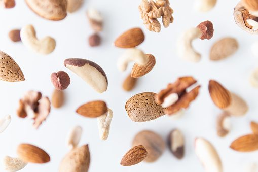 Assortment of mixed nuts flying above white background, levitation effect.