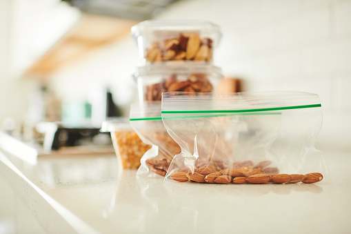 Assorted nuts in plastic containers on a counter in a bright modern kitchen