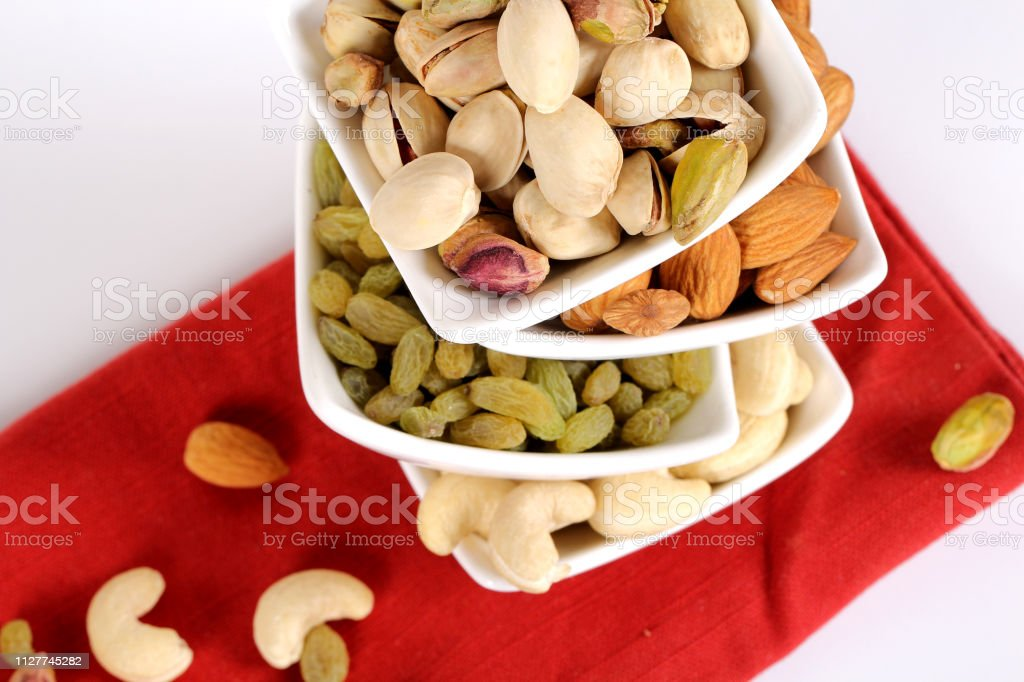 Assorted nuts on white, dry fruits, mix nuts, almond, cashew,...