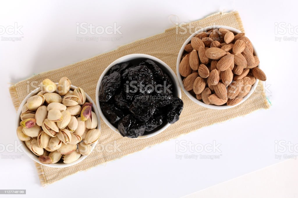 Assorted nuts on white, dry fruits, mix nuts, roasted almond, prunes,...