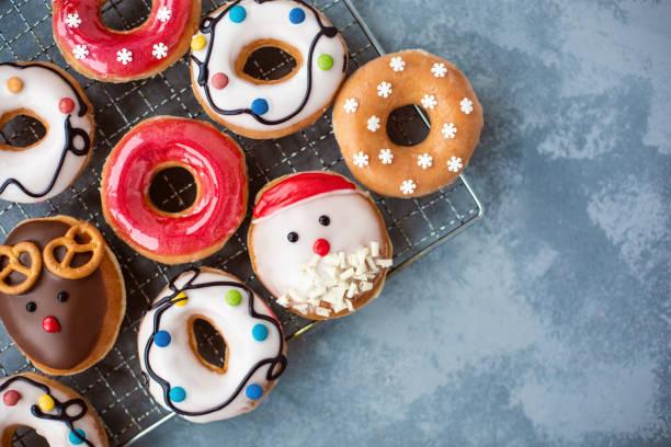 verglaste weihnachten und neujahr donuts auf grauen tabelle sortiert. flach zu legen. - aufstrich weihnachten stock-fotos und bilder