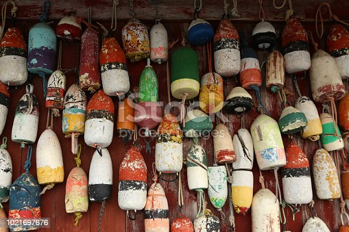 Assorted old lobster buoys hanging on wall