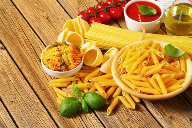 Assorted pasta, tomato passata and olive oil Assorted pasta, tomato passata and olive oil on wooden background uncooked pasta stock pictures, royalty-free photos & images
