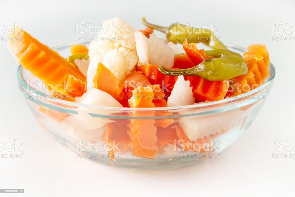 Assorted pickles vegetables carrot, chilli, cauliflower in glass bowl. Top view. Isolated. Copy space. stock photo