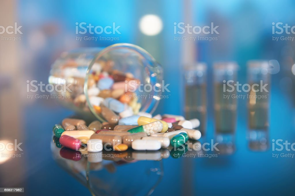 Assorted pills or capsules with medications on dark abstract background stock photo