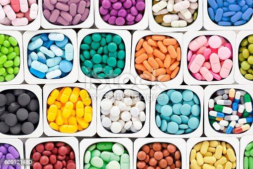 Varieties of multicolored pills inside plastic container