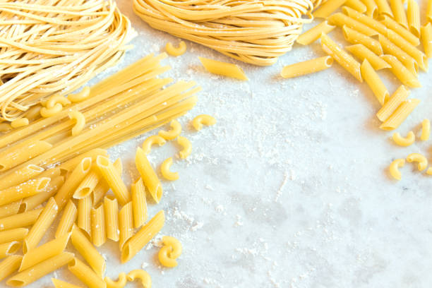 Assorted Raw Pasta Assorted italian Raw Uncooked Pasta on white background with copy space for text uncooked pasta stock pictures, royalty-free photos & images