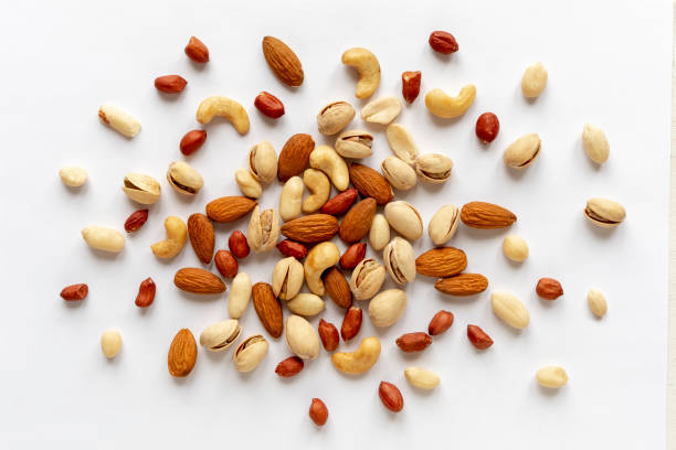 Assorted roasted and raw nuts scattered on white stock photo
