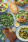 Assorted salads with fresh ingredients on the table with grilled steak, chicken brest and salmon, clean eating concept