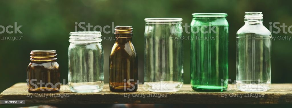 Assorted series collection of empty transparent glass bottle container in white, green and brown color, container reuse concept, eco friendly concept stock photo