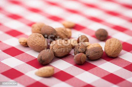 Horizontal photo of assorted nuts in shells on red gingham tablecloth with blurred background
