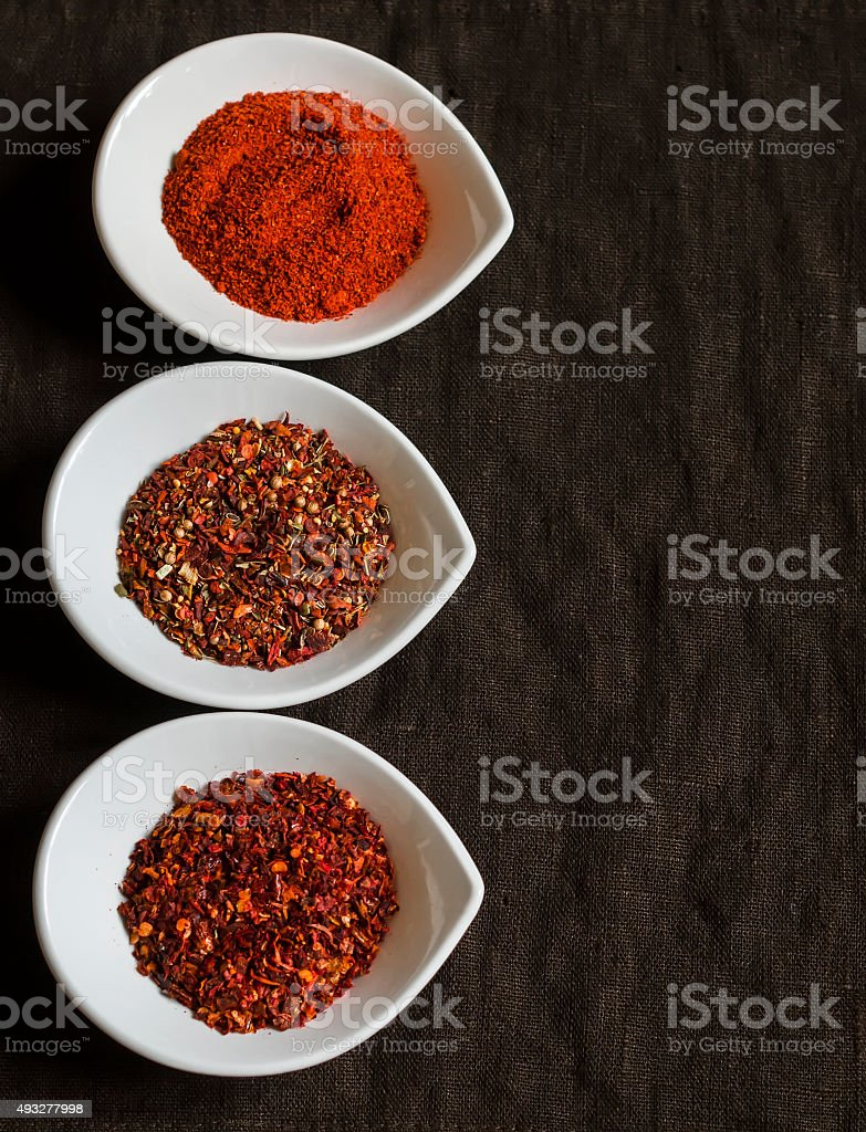 assorted spices in white bowls on a dark wooden surface stock photo