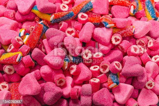 istock Assorted tasty gummy candies. Pink jelly sweets background. 1340292837