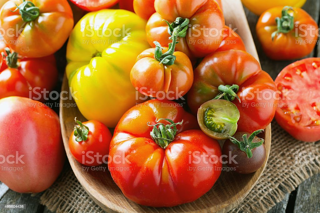 assorted tomatoes on wooden surface stock photo