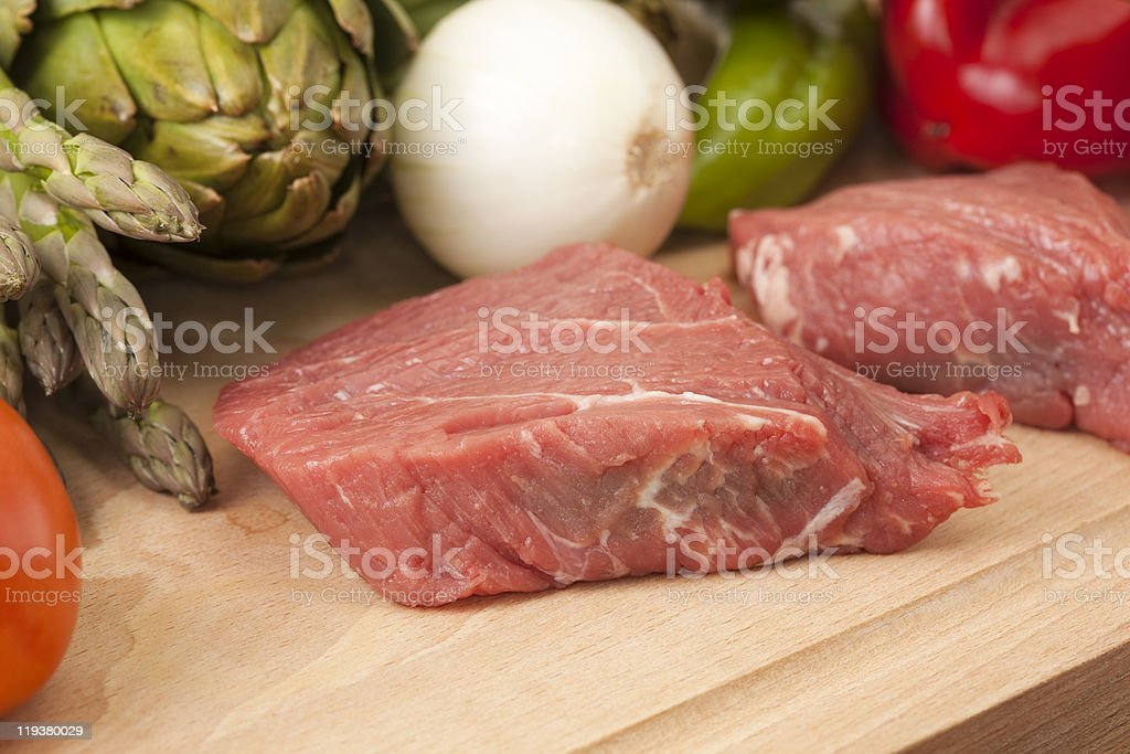 Assorted vegetables and sirloin steak on a cutting table royalty-free stock photo